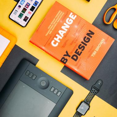 libro de diseño tablet y reloj sobre una mesa
