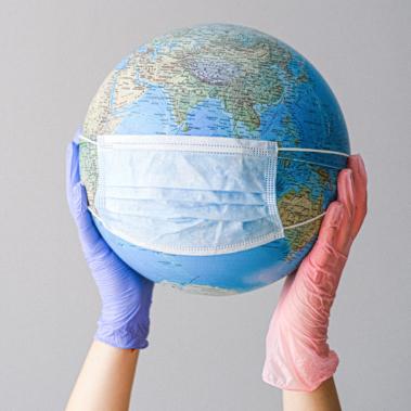 globo del mundo con mascarilla sujetado por manos con guantes